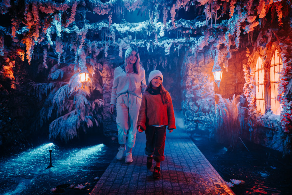 Parent with child walking through Snow Kingdom waterfall